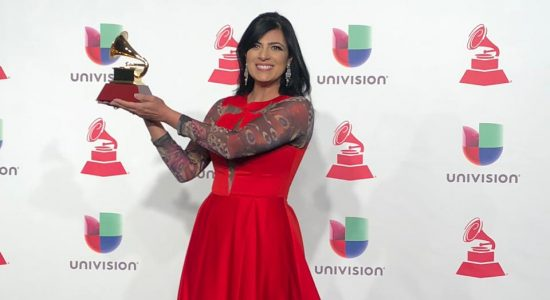 Fernanda Brum exibe seu vestido vermelho e o prêmio que levou