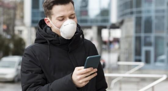 Homem olha para o celular de máscara