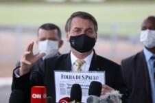 Bolsonaro segurando uma página da Folha de SP