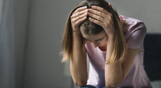 close-up-de-um-triste-mulher-jovem-segurando-dela-cabeca_23-2147953216