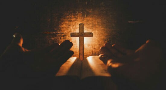 foco-de-imagem-conceitual-na-luz-de-velas-com-mao-de-homem-segurando-uma-cruz-de-madeira-na-biblia-e-mundo-turva_1150-9230