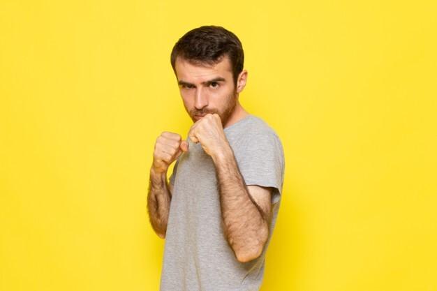 um-jovem-do-sexo-masculino-em-uma-camiseta-cinza-posando-com-um-estande-de-boxe-na-parede-amarela-homem-expressao-emocao-cor-modelo_140725-26523