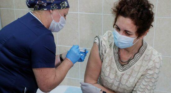 Profissional de saúde russa aplica vacina em paciente