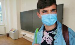 Estudante usando máscara com mochila nas costas na sala de aula