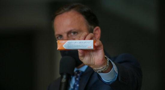 Governador João Doria com uma caixa da vacina CoronaVac na mão