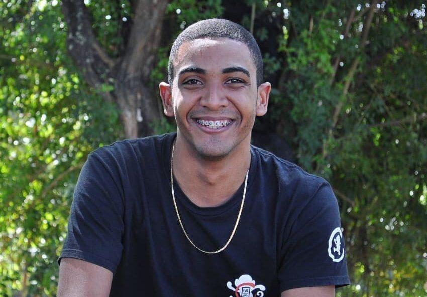 jovem negro sorrindo com árvores ao fundo