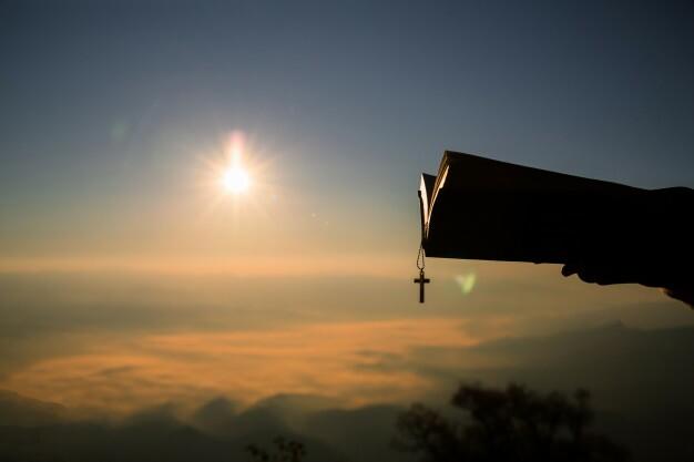 silueta-de-mao-humana-segurando-biblia-e-crucifixos-a-fundo-e-a-amanhecer_1150-7211