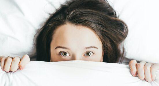 mulher deitada sob o cobertor