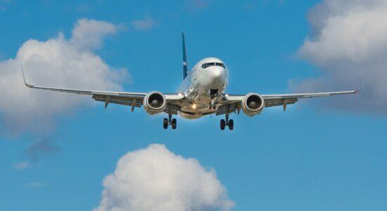 avião voa entre nuvens no céu azul
