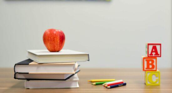 livros, maçã, lápis e cubos sobre a mesa da escola