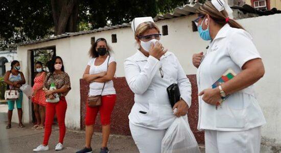 enfermeiras esperam ônibus em Havana, cuba