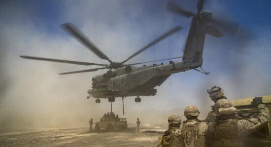 Exército em clima desértico com helicóptero e jipes