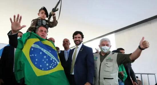 Presidente Jair Bolsonaro ao lado de criança fardada