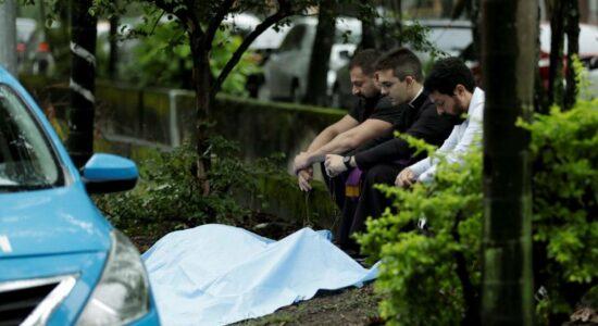 Médico Cláudio Marsili é assassinado a tiros na Barra. Seu filho, o também médico Ítalo Marsili (à esquerda), reza perto do corpo do pai